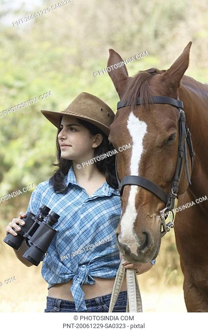Teenage girl standing with a horse and holding a pair of binoculars