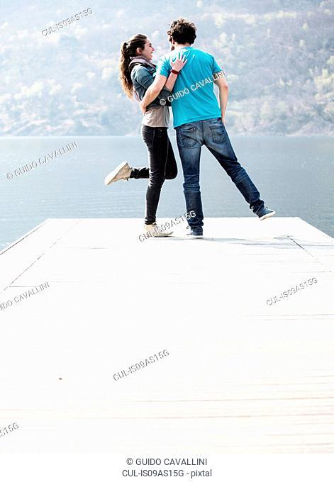 Young couple standing on one leg on pier at Lake Mergozzo, Verbania, Piemonte, Italy