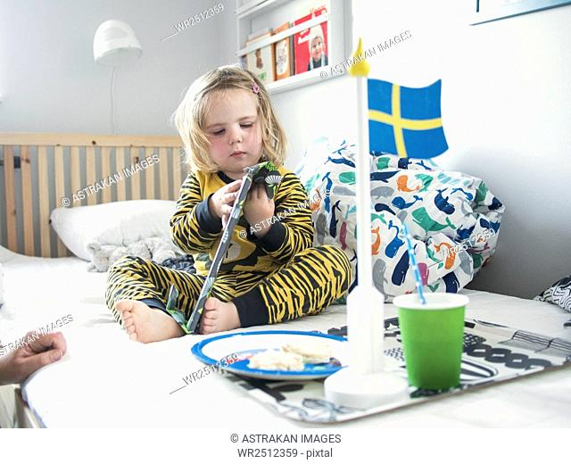 Girl holding toy while having breakfast on bed
