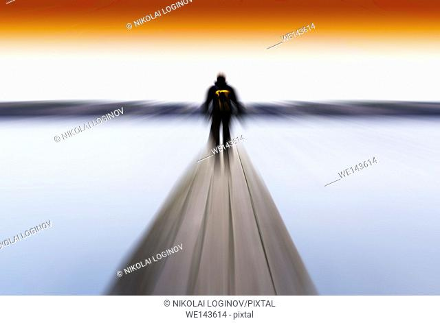 Horizontal radial blur man on pier abstract with orange sky background