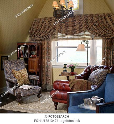 Swagged patterned curtains in livingroom with leather armchair and patterned upholstered Edwardian armchair