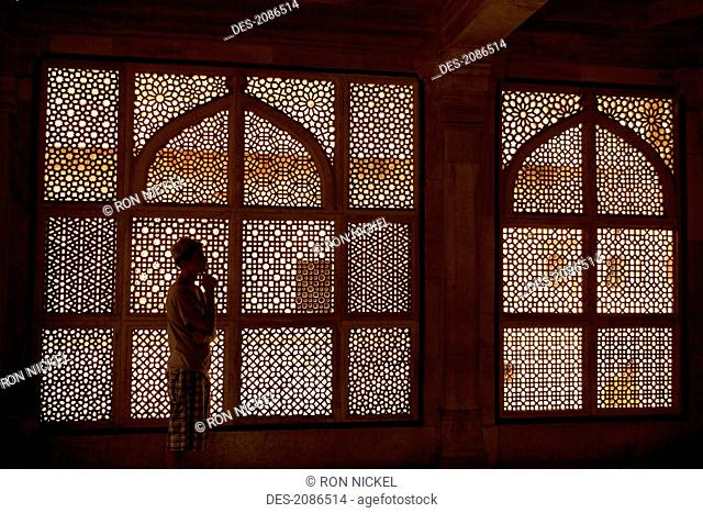 A young man stands in front of an ornate screened window, jaipur rajasthan india