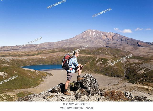 New Zealand, North Island, Man hiking at tongariro national park with mount ruapehu in background