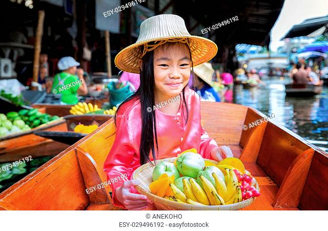 Chikd sit on the boat and hold the fruit basket in Traditional floating market , Thailand