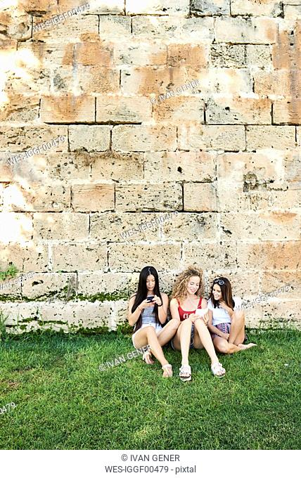 Three young women sitting at stone wall using cell phones listening to music
