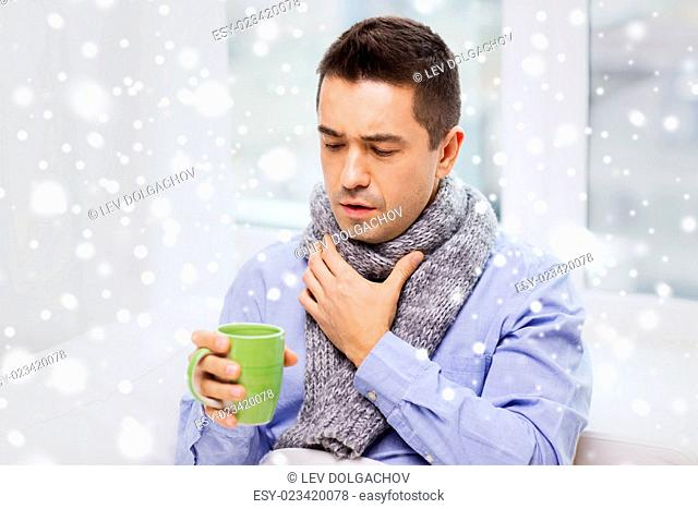 health care, people, winter and medicine concept - ill man with flu coughing and drinking hot tea from cup at home over snow effect