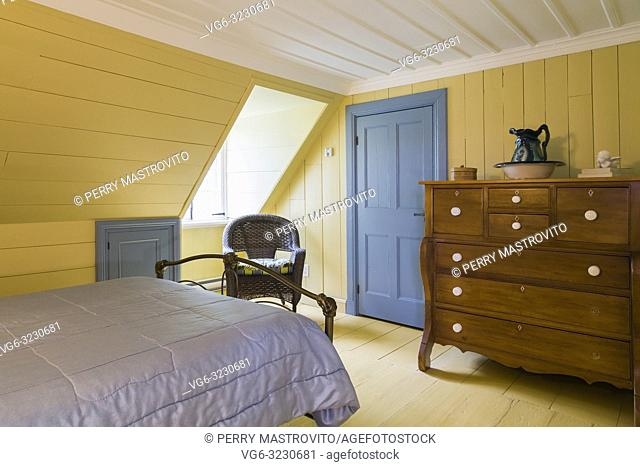 Double bed with antique brass metal footboard, wooden dresser and wicker chair in upstairs master bedroom inside an old 1809 French regime cottage style home