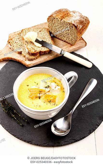 traditional scottish fish soup, cullen skink, with potatoes in a gray clay cup on a round slate and home baked soda bread on wooden board