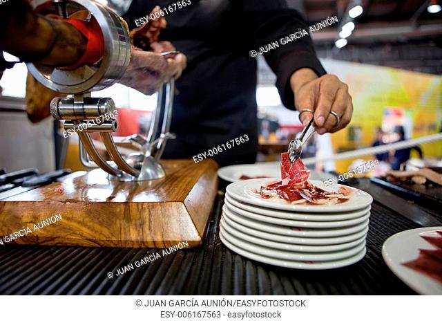 Waiter serving acorn-fed Iberian ham, Spain