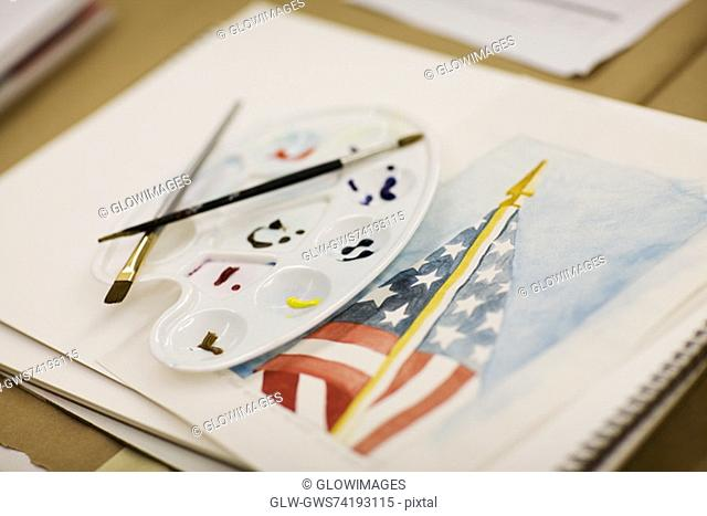 Paint brushes and a palette on an American flag painted on a sketch pad