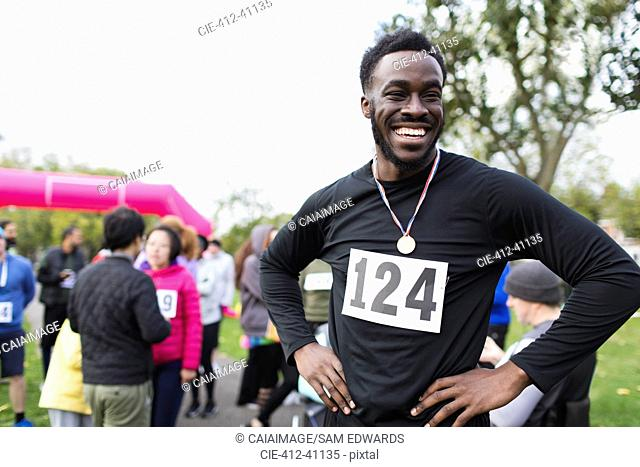 Portrait happy, confident male runner wearing medal at charity run in park