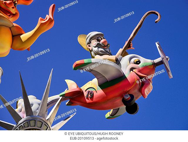 Papier Mache figure flying an airplane resembling a fish during Las Fallas festival