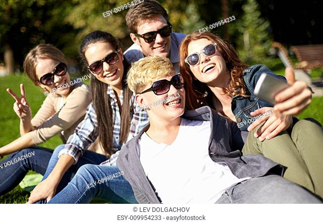 summer, technology, education and teenage concept - group of happy students or teenagers with smarphone taking selfie at campus