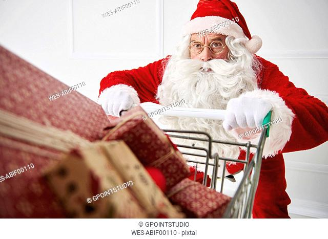 Portrait of Santa claus with shopping cart of Christmas presents