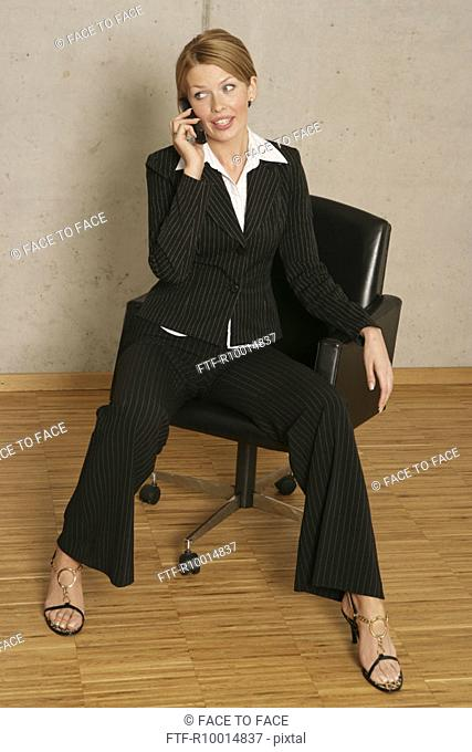A blonde businesswoman sitting on chair as she converses on the phone