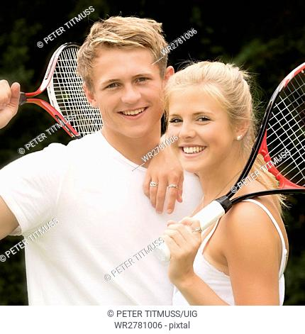 Portrait of two young tennis players holding their racquets