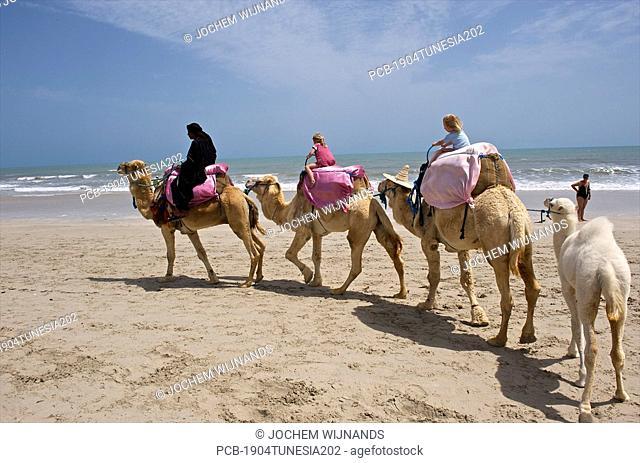 Tunesia, Djerba, Midoun, children enjoying a camel ride on the beach