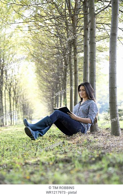 A woman sitting reading a book under the trees
