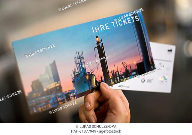 A woman holds up a ticket for the Elbe Philharmonic Hall at Kulturcafé in Hamburg, Germany, 20 June 2016. The ticket sales started half a year prior to the...