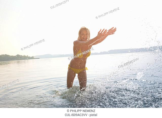 Young woman splashing water in lake