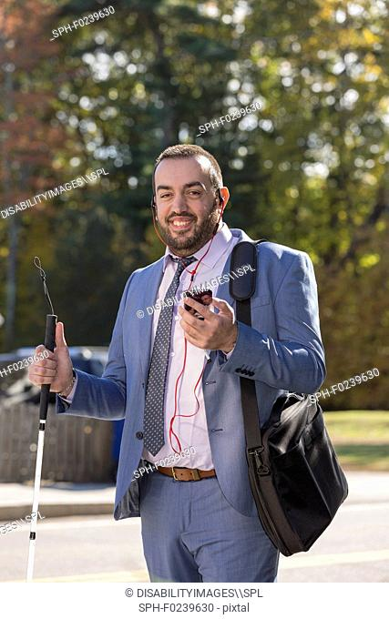 Businessman with visual impairment listening to his phone and using cane