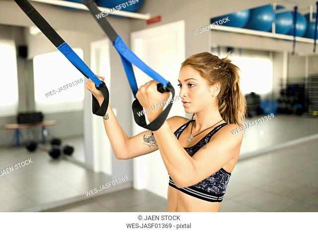 Young woman doing suspension training in gym