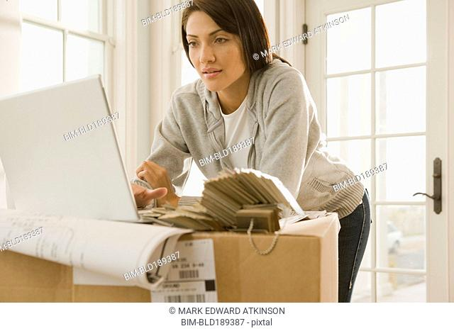 Hispanic woman using laptop on boxes