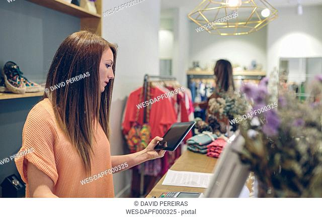Shop assistant using tablet at counter in a boutique