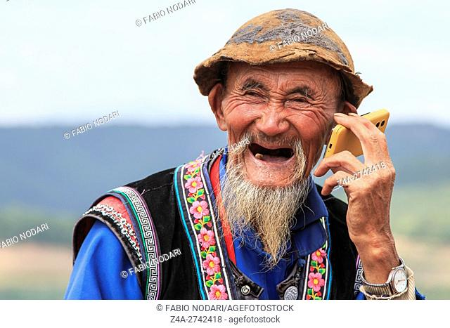 An old chinese man dressed with the traditional attire using a telephone while enjoying the panorama of DongChuan in Yunnan Province, China