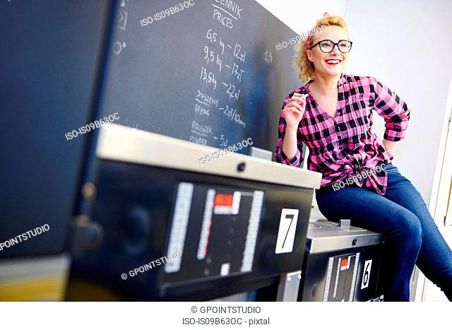 Female laundrette owner sitting on top of washing machine by chalkboard