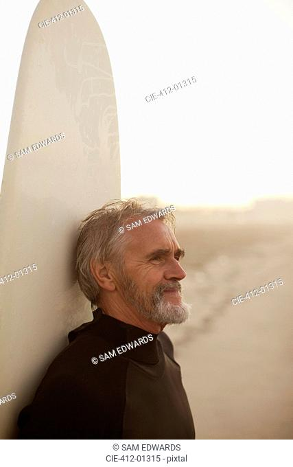 Older surfer leaning on board on beach
