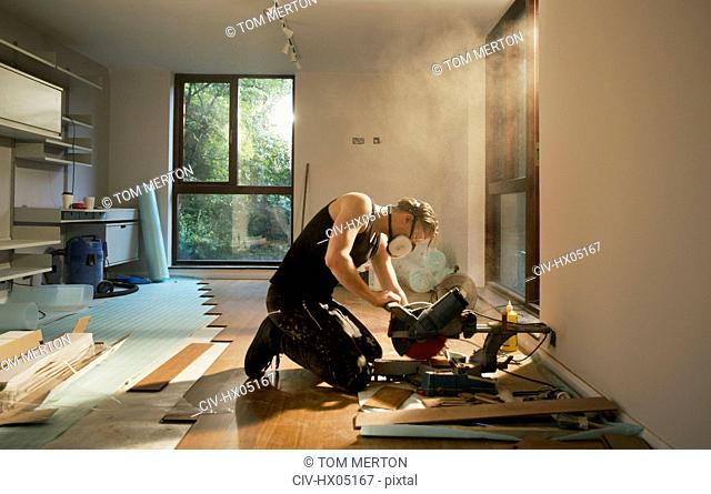 Construction worker using electric saw to cut hardwood flooring in house