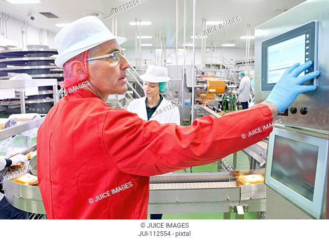 Worker at control panel at production line in cheese processing plant