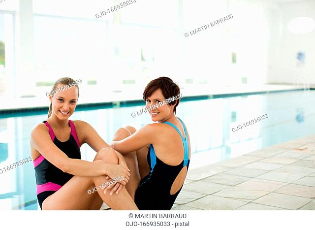Portrait of smiling women in bathing suits at poolside