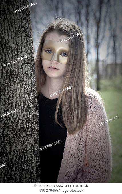 Teenage girl wearing a mask and standing behind a tree