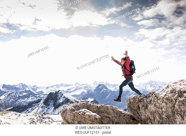 Germany, Bavaria, Oberstdorf, woman jumping on rock in alpine scenery