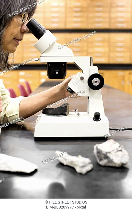 Filipino scientist using microscope in laboratory