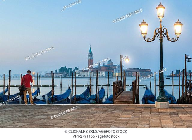 A solitary man is waiting in front of the gondolas docked along the Riva degli Schiavoni. in the background the island of San Giorgio Maggiore, Venice, Italy