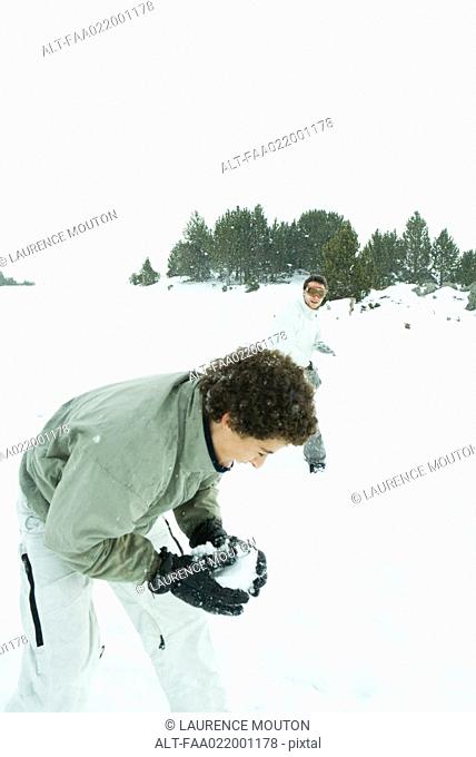 Young friends having snowball fight in snow