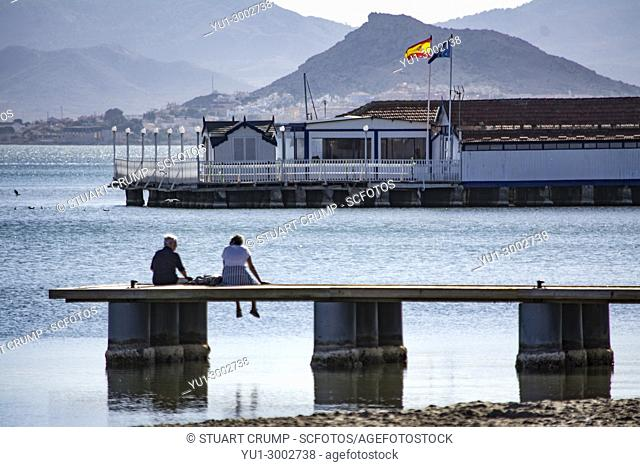 Couple sitting on the Jetty looking over the Mar Menor at Los Alcazares in Murcia Spain