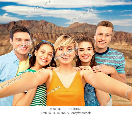 happy friends taking selfie over grand canyon