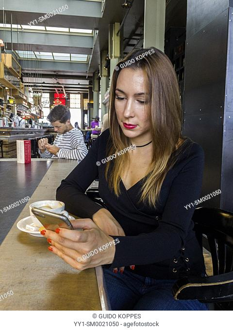 Rotterdam, Netherlands. Young, brunette and caucasian woman using her smartphone while having a coffee in Hotel New York