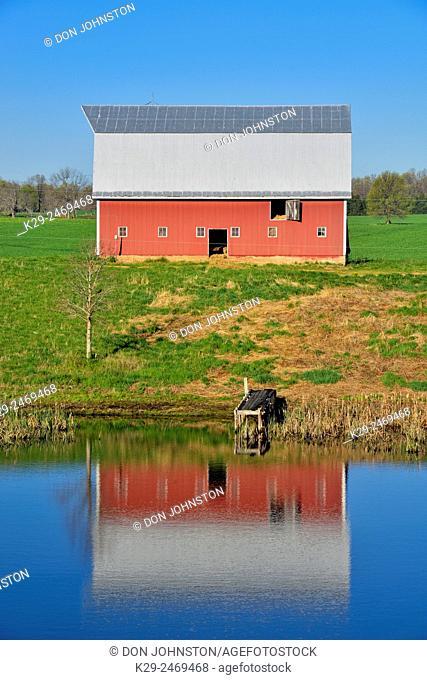 Red barn reflected in White Oak Pond, near Lebanon, Missouri, USA