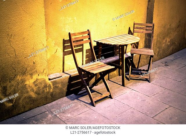 Two wooden chairs and a wooden table near a wall. Barcelona, Catalonia, Spain
