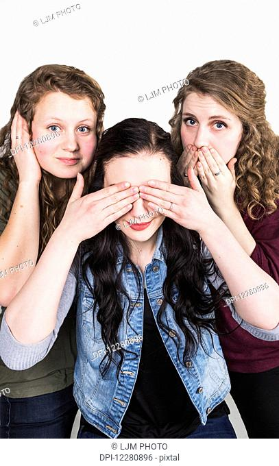 Three young women doing humorous pose of Hear no evil, see no evil, speak no evil; Alberta, Canada