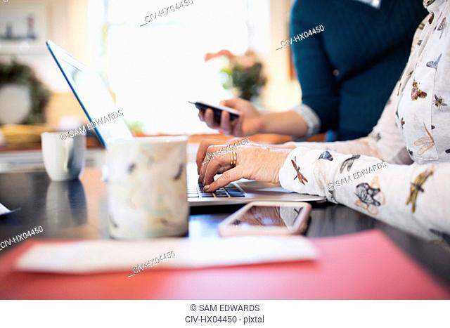 Senior woman using laptop in kitchen