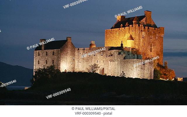 Zoom back to reveal Eilean Donan Castle at night, Kintail National Scenic Area, Dornie, western Highlands, Scotland