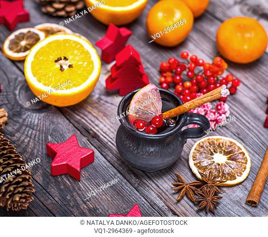 Mulled wine in a brown ceramic cup on a gray wooden background and Christmas decorations