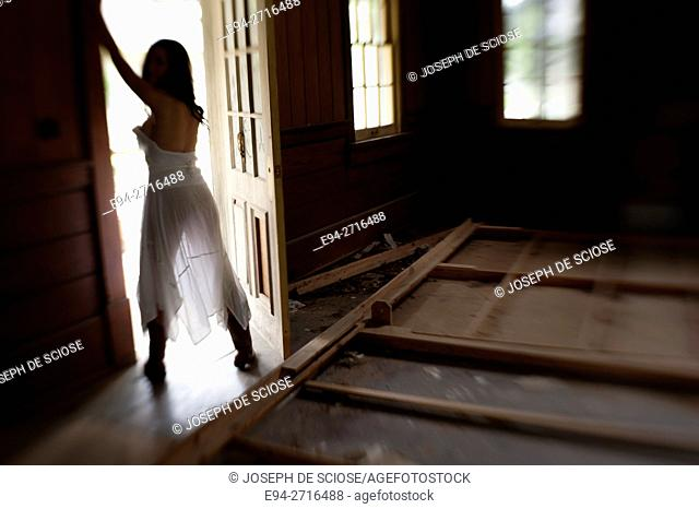 Silhouette of woman wearing a white dress standing in the doorway of an old house