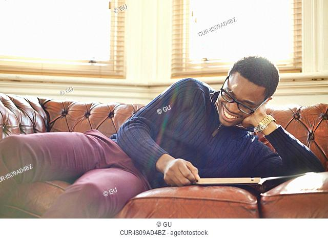 Young man enjoying reading on sofa